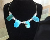 This piece of jewelry is a pretty silver choker with blue-green stones separated by glass and silver beads