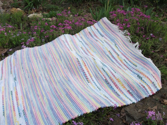 Hand woven, rag rug, in rainbow colors, with hem stitching and fringe