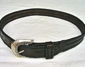 Leather belt with edge braiding and center applique braiding.