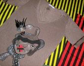 handbemaltes kurzärmeliges Damenshirt mit Frauenportrait und Federbrosche