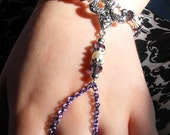 Slave style purple chain bracelet with fleur de lis metal center piece and metal and crystal beads with lobster claw clasp.