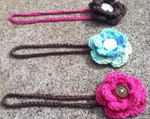 Brown crocheted headband with attached pink flower