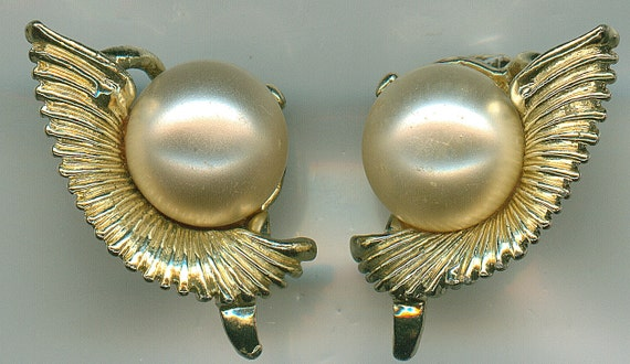 Vintage gold toned metal clip on earrings in a shell style with a large faux pearl