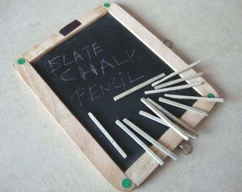 Chalk Pencils cut from natural Chalk stone laid out on a primitive slate board
