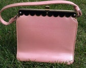 Vintage 1950s pink patent handbag with black and gold detailing on the top