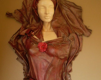 Leather sculpture of a red and bronze lady.