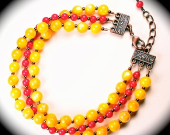 3 strand yellow and red beaded bracelet with antiqued brass clasp and brass seed beads.