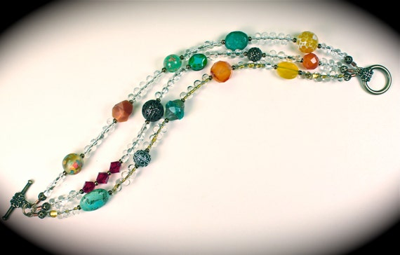 Beaded three strand bracelet with turquoise, vintage beads, Swarovski crystals, sterling, antiqued brass filigree beads and brass toggle.