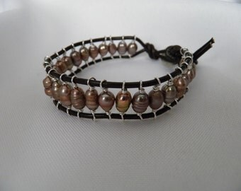 "Bracelet... ""Caged Pearls""  26 bronze pearls wire wrapped and then strung on brown leather cord with button closure bracelet."