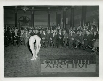 THE CONTORTIONIST - 1930s - men watch as a young woman displays her flexibility - B&W Photograph