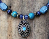 Blue beaded neckace with pendant.