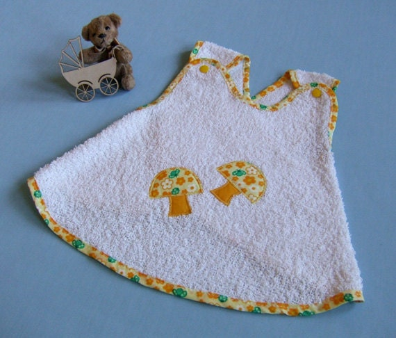 White and yellow terry cloth baby bib with mushrooms appliques and yellow buttons