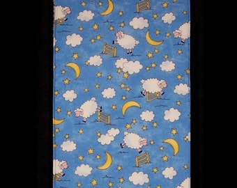 Burp Cloth Counting Sheep features sheep jumping over fences under a blue sky filled with bright clouds, bright yellow moon and stars, BC020