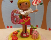 Blond little girl with cupcake and lollipop