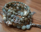 Set of 5 aqua terra jasper, amazonite, and cream turquoise gemstone beaded bracelets with charms and silver tassel.