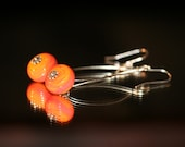 Handcrafted sunset orange and pink lampwork glass earrings on silver metal loops