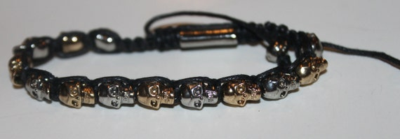 Silver and gold skull bracelet in black
