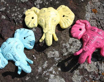 A Trio of Elephant Heads/Wall Hook/Coat Hook/Cast Iron in Berry Pink, Sea Blue and Yellow