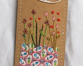 Hand-stitched label with pretty feedsack and lots of embroidery