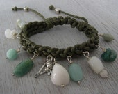 Green Makramebracelet with green and white stone pendants and tibetian silver charms