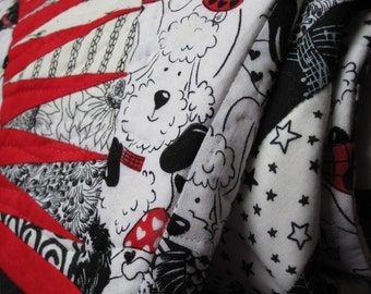 Lap quilt that features puppies and is black and white and red allover...