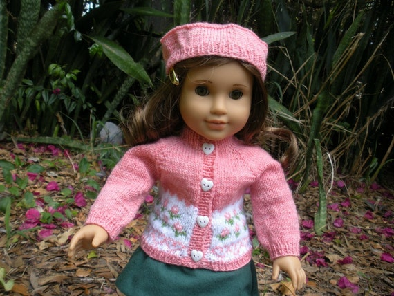 """Handknitted, peachcolored sweater with flower design and matching hat and a green  A-line skirt for American Girl doll and other similar 18"""""""