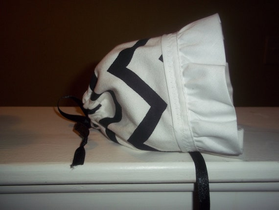 Fun baby bonnet.  Bold black and white zig zag bonnet.  Wide white rufffle and tied with a satin ribbons