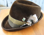 Brown velour hat with feathers on a stick pin
