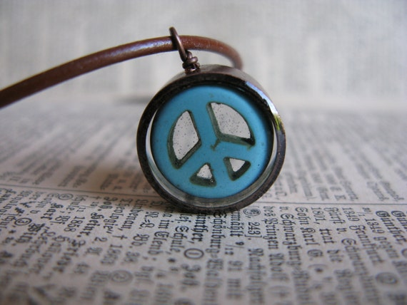 Peace sign turquoise bead  encased in resin with open back  copper bezel