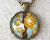 Necklace of orange and sky blue cherry blossoms in old gold setting