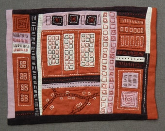 Mini art quilt,hand-stitched with appliqued geometric, map like shapes.