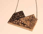TRINTA necklace is in wood with an original design silkscreen printed on it.