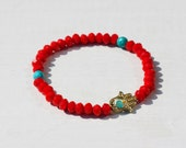 A hamsa charm with firey red and turquoise beads beaded bracelet