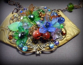 Necklace, mixed media of polymer and vintage glass flowers on Brass filligree with chrystals