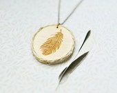 WoodPendant with engraved feather and the edge of the twine