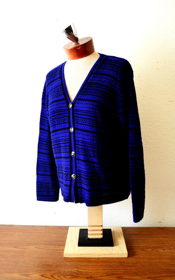 A deceivingly vibrant purple, knitted, button up cardigan with eclectic horizontal patterns