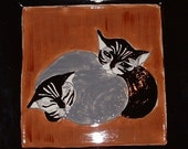 Black and Grey Cats on Orange and Black Platter