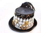 Steampunk hat size 59cm with white guipure lace, gold coloured cogs, feather plume. Victoriana style.  Embellished with Swarovski crystals.