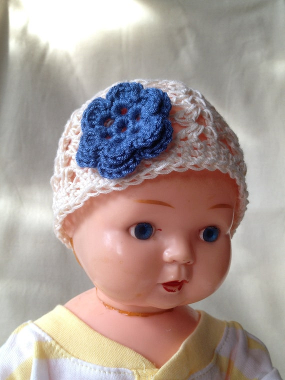 White crocheted hat with blue flower for newborn baby