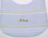 Baby bib in blue gingham fabric, accented with 3 pretty yellow flowers applique, ribbon, and lace.