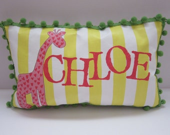 Baby pillow in bright yellow stripes with pink giraffe accent. Personalized with name.