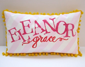 Baby pillow in light pink stripes with bright pink personalized name.