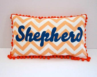 Baby pillow in dreamsicle orange chevron and navy blue script. Personalized with name.