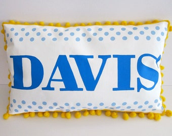 Baby pillow in bright blue lettering with light blue polka dots. Personalized with name.