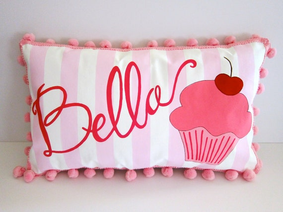 Baby pillow in light pink stripes with bright pink cupcake. Personalized with name.
