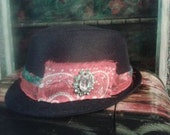 black fedora hat with red bandanna, recycled fabric, and green broach