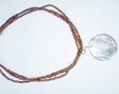 Three strand glass seed beads with a shell pendant