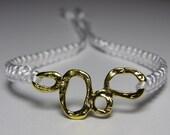 White bracelet with bubbly goldish finding