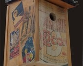 """Birdhouse, Salt box style with corrigated roof. """"Vintage Ad Board"""" face with travel poster apliques"""