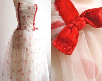 1950's strapless cocktail dress in white voile with red polka dots and red velvet ribbon and bow detail on bust, size 10.